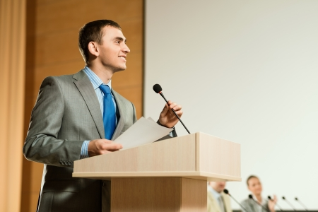 presentation board: male speaker looks into the room and said into the microphone, speech at the conference