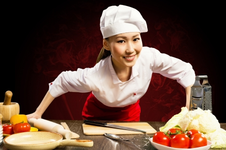 leaned: Asian woman cook leaned over the table and looking into the camera Stock Photo