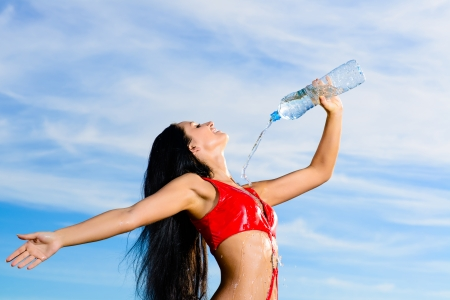 wideview: Young female sport girl in red uniform with a bottle of water