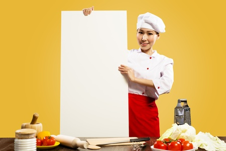Asian female chef holding a white poster for the text on the table laid out the ingredients for cooking photo