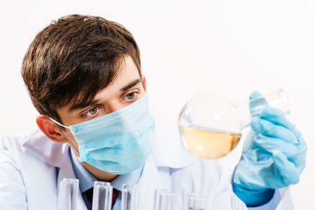 scientist working in the lab, in protective mask, examines a test tube with liquid Stock Photo - 17572979