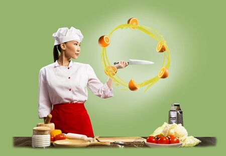 Asian female chef holding a knife, around which revolve sliced  oranges photo