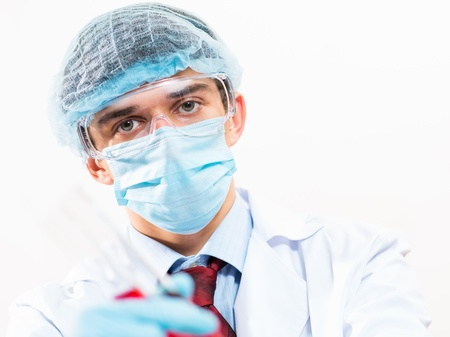 scientist working in the lab, in protective mask and cap, examines a test tube with liquid Stock Photo - 17572961