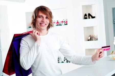 Young man at shopping mall checkout counter paying through credit card Stock Photo - 17573639