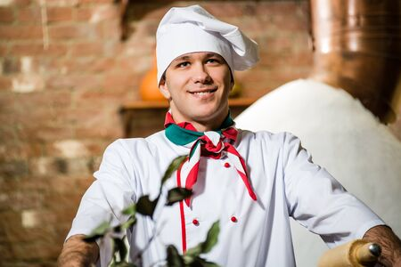 relies: portrait of a cook, is on the traditional kitchen relies hands on the table
