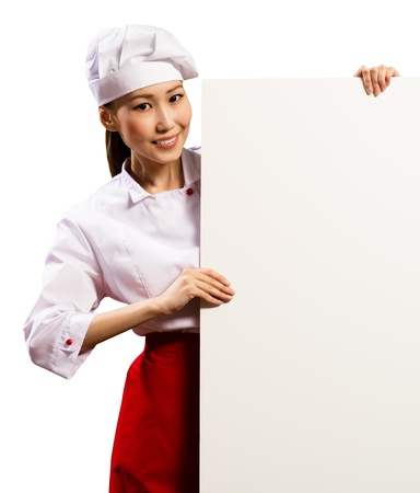 female chef holding a poster for text, look at the camera and smiling Stock Photo