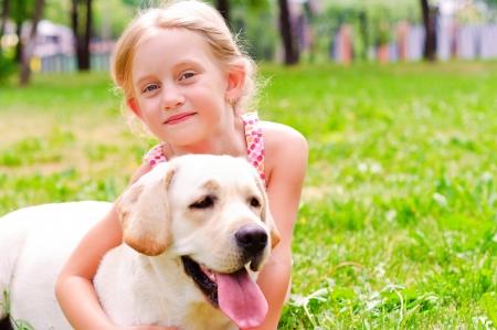 menina e ela lablador, abraçando no parque deitado na grama Imagens