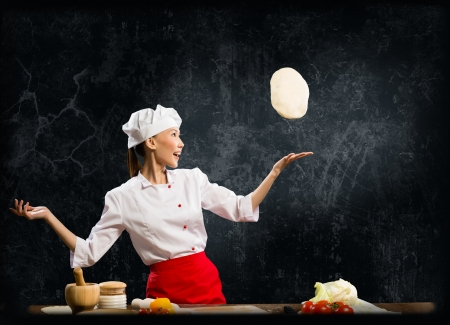Asian female chef tosses a piece of dough, creative cooking photo