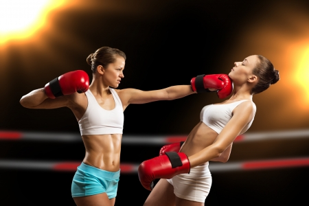 Aggressive boxing woman, hits an opponent in the head photo