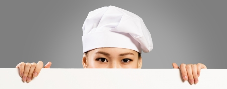Asian female chef holding a white banner for text, hiding her face behind a poster, you can see only the eyes photo