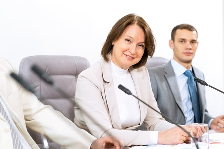 Portrait of a senior business woman at the meeting, sitting at a table on which are microphones photo