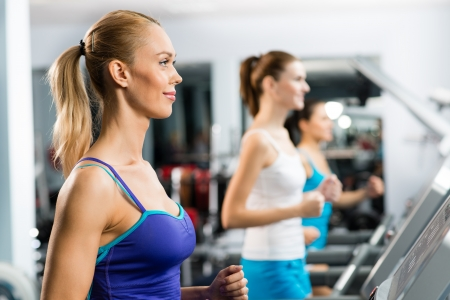 women running on a treadmill in a fitness club, sport in the fitness club photo