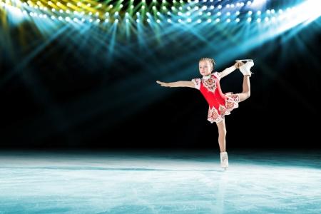 patinaje: joven patinadora realiza en el hielo en el fondo iluminaci�n luces