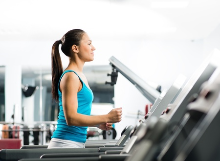 attractive young woman runs on a treadmill, is engaged in fitness sport club