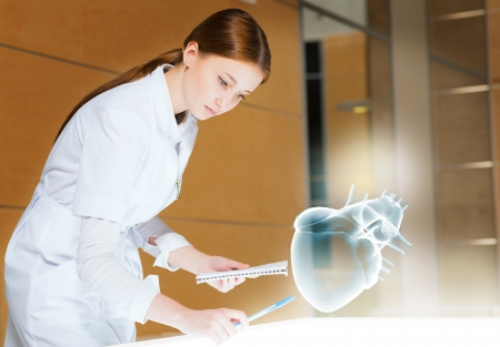 young woman leaning over a medical researcher illuminated table, the concept of modern technology in medicine photo