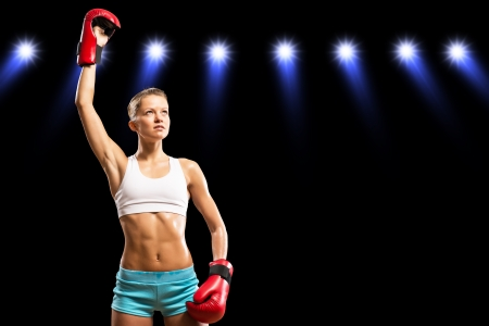 female boxer is in the rays of lights, raised a hand in a glove photo