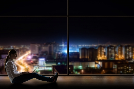 young woman sitting with a laptop by the window with a night city Stock Photo - 18635540