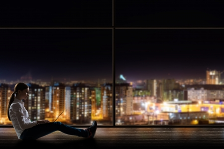 young woman sitting with a laptop by the window with a night city