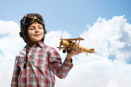 airman: Boy in helmet pilot playing with a toy wooden airplane in the clouds, dreaming of becoming a pilot