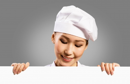 female chef holding a poster for text, look at the poster and smiling photo