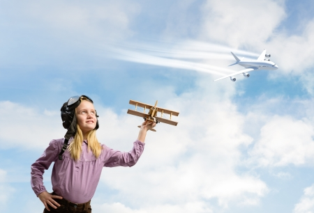 inair: little girl in aviator helmet holding a toy plane against the airplane is flying in the sky
