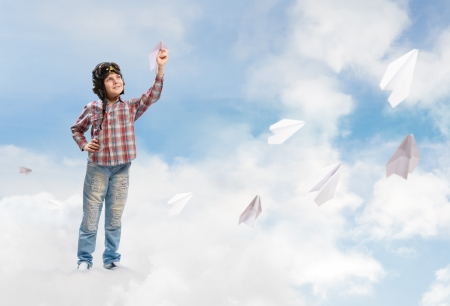 inair: Boy in helmet pilot launches paper airplanes in the clouds Stock Photo