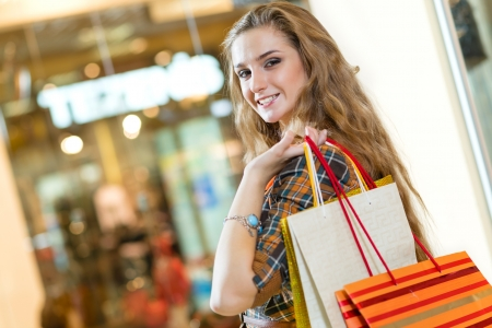 portrait of a beautiful woman in a shopping center, holding shopping bags and smiling photo