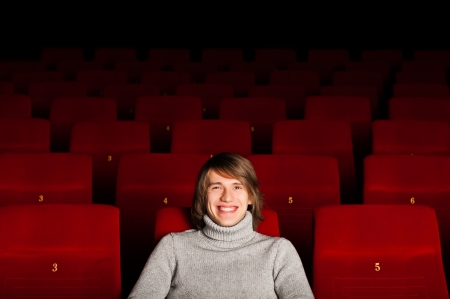 young man in casual sitting in the cinema and watching a movie photo