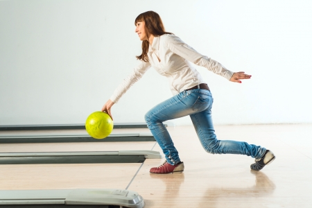 bowler: pleasant young woman throws a bowling ball, looks at the target and smiling