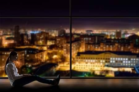 young woman sitting with a laptop by the window with a night city Stock Photo - 18787972