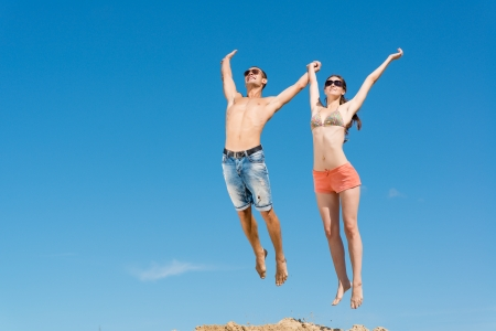 young couple jumping together on a blue sky background photo