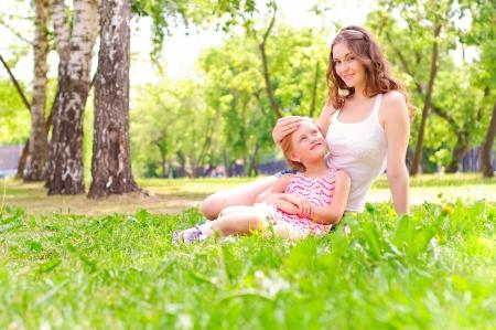 madre e hija: madre e hija sentados juntos en la hierba, y pasar tiempo con la familia Foto de archivo
