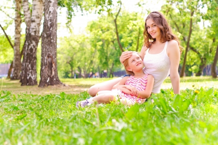 mother and daughter: mother and daughter sitting together on the grass, and spend time with family Stock Photo
