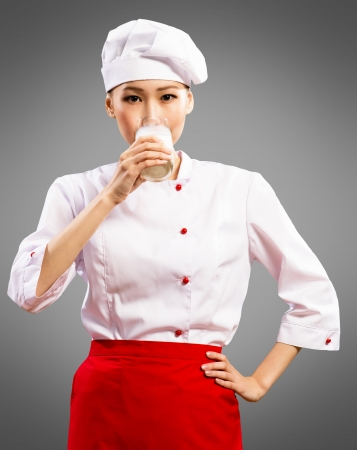 Portrait of Asian cooks, drink a glass of milk photo