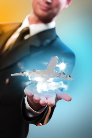 piloto de avion: piloto en forma de extender la mano a un avi�n que vuela con el cielo, las nubes y el sol