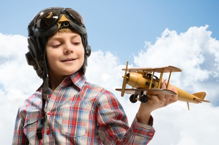 Boy in helmet pilot playing with a toy wooden airplane in the clouds, dreaming of becoming a pilot