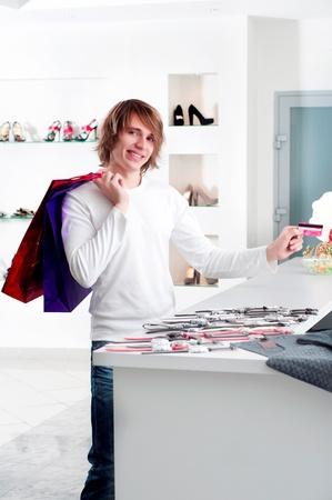 Young man at shopping mall checkout counter paying through credit card photo
