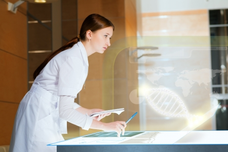 young woman leaning over a medical researcher illuminated table, the concept of modern technology in medicine Stock Photo