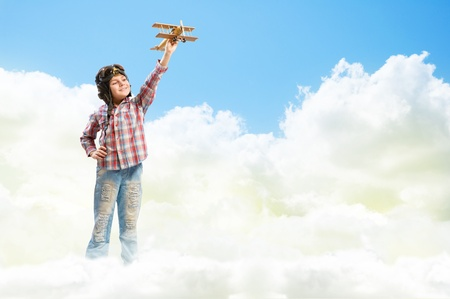inair: Boy in helmet pilot playing with a toy wooden airplane in the clouds, dreaming of becoming a pilot