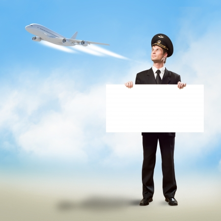 pilot in the form of holding an empty billboard on the background of sky and flying plane, place for text photo