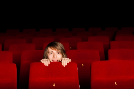 young man in the cinema hiding behind a chair, watching scary movie photo