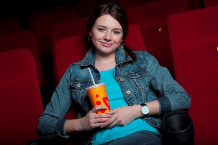 beautiful woman in a movie theater, watching a movie and drink a drink photo