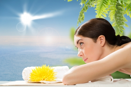 beautiful spa woman lying on the couch, in front of her flower and rolled towel Stock Photo - 19029226