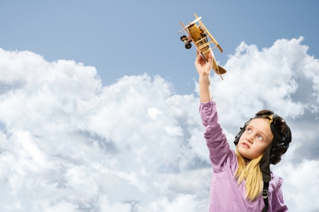 girl in helmet pilot playing with a toy wooden airplane in the clouds, dreaming of becoming a pilot photo