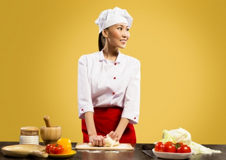 Asian female chef cooking pizza dough, smiling and happy