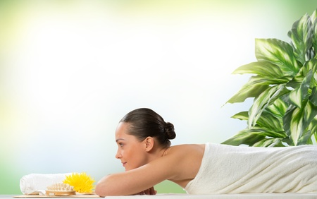 beautiful spa woman lying on the couch, in front of her flower and rolled towel Stock Photo - 19056658