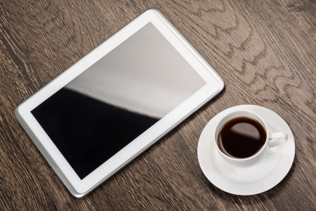 tablet and cup of coffee are on the table, still life photo
