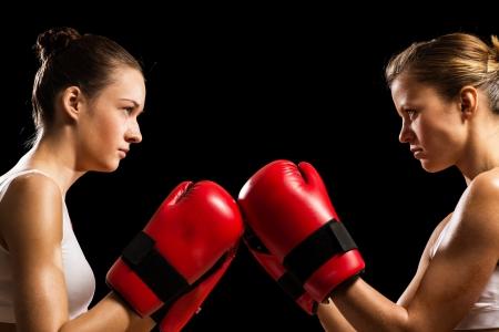 guantes de boxeo: dos boxeadoras se enfrentan entre s�, empujando los guantes de boxeo, iniciar una pelea Foto de archivo