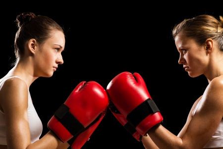 two female boxers face each other, pushing the boxing gloves, start a fight Stock Photo