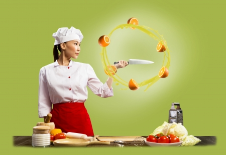 revolve: Asian female chef holding a knife, around which revolve sliced ​​oranges Stock Photo